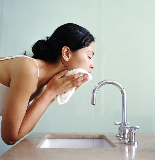 Woman washing face with wash cloth over sink, side view